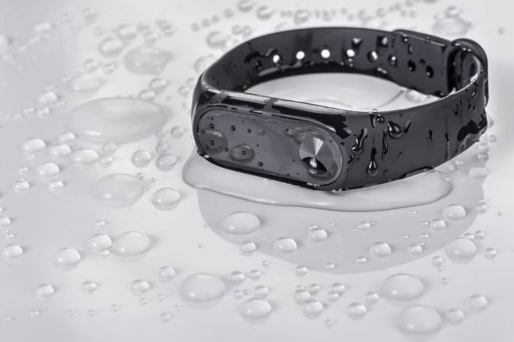 Fitness bracelet on a white glossy background with drops of water